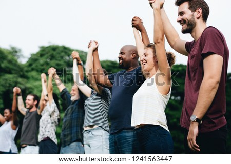 Happy diverse people holding hands in the park