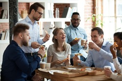 Happy diverse team people talking laughing at funny joke eating ordered pizza in office, friendly employees group enjoy positive emotions sharing lunch together having fun at work break on friday