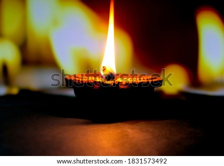 Happy Diwali. Clay diya candle illuminated in Dipavali, Hindu festival of lights. Traditional oil lamp on dark background Stock photo ©