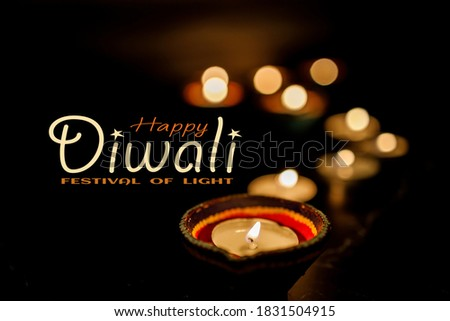 Happy Diwali - Clay Diya lamps lit during Dipavali, Hindu festival of lights celebration. Colorful traditional oil lamp diya on dark background. Copy space for text. Stock photo ©