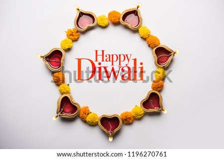 Happy Diwali Greeting Card made using sweets, or fire crackers or Diya or flowers, selective focus