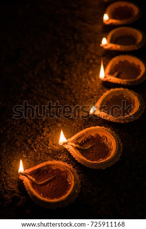Happy Diwali - many Terracotta diya or oil lamps arranged over clay surface or ground in one line or curved or zigzag form, selective focus #725911168