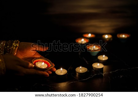 Happy Diwali - Woman hands with henna holding lit candle isolated on dark background. Clay Diya lamps lit during Dipavali, Hindu festival of lights celebration. Copy space for text. Stock photo ©
