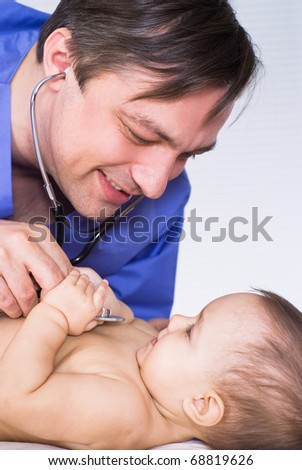 happy doctor examining newborn on a white