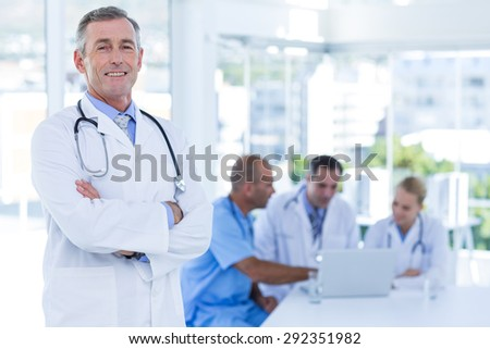 Happy doctor looking at camera with arms crossed while his colleagues works in medical office