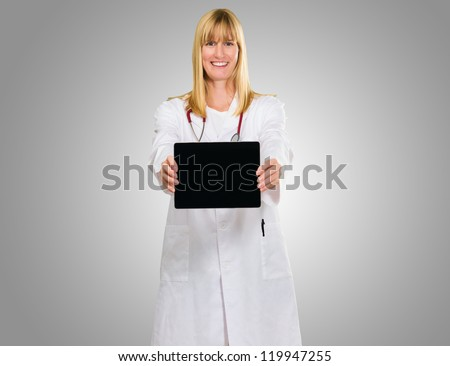 Happy Doctor Showing Digital Tablet against a grey background