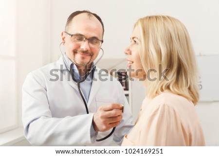 Happy doctor with stethoscope checking patient heart beat or breath at hospital. Medicine, healthcare and people concept