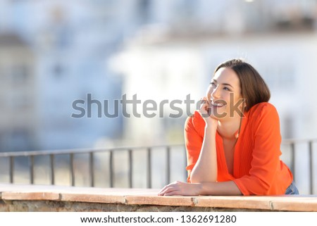 Happy dreamer dreaming looking at side in a balcony in a town outskirts