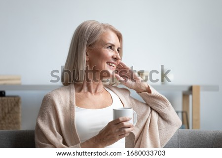 Happy dreamy middle aged woman sitting on comfortable sofa in living room with cup of black tea or coffee, looking away, Peaceful mature lady enjoying no stress calm positive pastime alone at home.