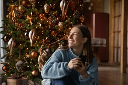 Happy dreamy millennial woman sit near Christmas tree use cellphone look in distance making wish. Smiling young female enjoy New Year winter holiday at home, dreaming or visualizing of joyful future.