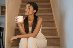 Happy dreamy multiracial woman sitting on wooden stairs at home with cup of black tea or coffee and looking away. Peaceful lady enjoying no stress calm positive pastime alone at home
