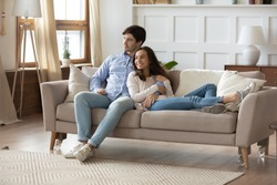 Happy dreamy young caucasian couple rest cuddle on couch in design living room thinking or visualizing, smiling millennial man and woman relax on sofa at home, hug and embrace, rental concept