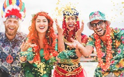 Happy dressed people celebrating at carnival party throwing confetti - Young friends having fun together at fest event - Youth, hangout, festive and happiness concept - Focus on left couple hands