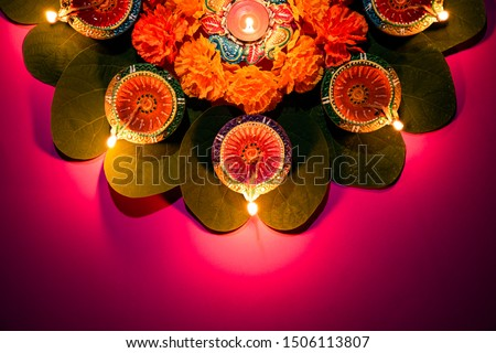 Happy Dussehra. Clay Diya lamps lit during Dussehra with yellow flowers, green leaf and rice on pink pastel background. Dussehra Indian Festival concept.