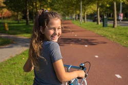 Happy dutch kid laughs. Beautiful little girl rides bike on bike path. Cyclist child or teenager girl enjoys good weather and cycling. Environmentally friendly transport concept. The Netherlands.