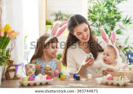 Happy easter! A mother and her daughter painting Easter eggs. Happy family preparing for Easter. Cute little child girl wearing bunny ears on Easter day. #383744875