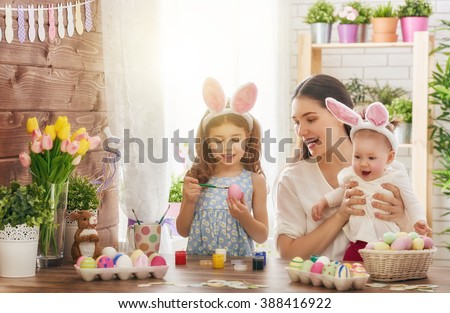 Happy easter! A mother and her daughter painting Easter eggs. Happy family preparing for Easter. Cute little child girl wearing bunny ears on Easter day. #388416922