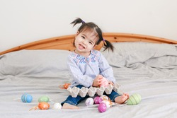 Happy Easter. Asian Chinese baby girl with funny pigtails sitting on bed at home and playing with colorful Easter eggs. Kid child celebrating traditional Christian holiday.