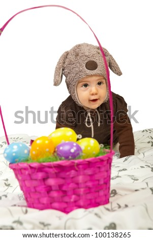 Happy Easter baby crawling to  basket with colorful eggs
