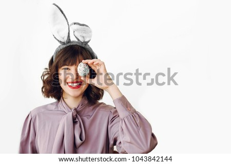 happy Easter. beautiful stylish girl in bunny ears holding colored easter egg on white background isolated. funny easter hunt concept. happy woman smiling with egg at face. fun moments #1043842144