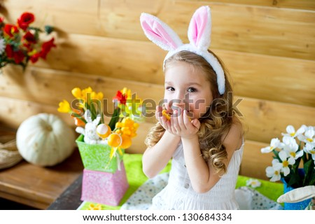 Happy easter bunny girl with easter eggs sitting in country house and celebrating easter
