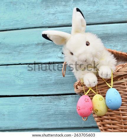 Happy Easter Bunny in a basket and eggs on a blue wooden background