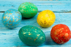 Happy Easter card. Colorful shiny easter eggs on wooden background. Copy space for text