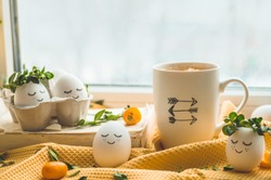 Happy Easter card. Cute Easter eggs with a painted face in a spring wreath, cup tea with kumquat. Happy easter.