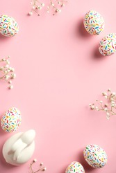Happy Easter card. Frame made of  colorful speckled Easter eggs, Easter bunny and spring flowers on pink background. Vertical banner mockup for social media stories.