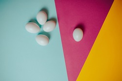Happy Easter card with copy space. White eggs on colorful background. Orange, pink, blue paper background.