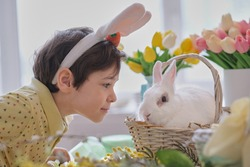 Happy easter. Child boy in bunny ears and hare sits in a wicker basket for spring holiday celebration. soft focus