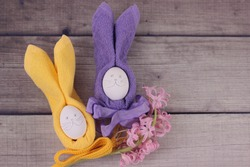 Happy easter concept.Easter holiday table setting with eggs on barn boards.Pink hyacinth, rabbits from eggs, yellow and purple napkins with bows on wooden background.Top view with copy space for text.