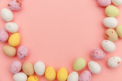 Happy Easter concept. Preparation for holiday. Easter candy chocolate eggs and jellybean sweets isolated on trendy pastel pink background. Simple minimalism flat lay top view copy space