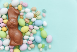 Happy Easter concept. Preparation for holiday. Easter candy chocolate eggs bunny and jellybean sweets isolated on trendy pastel blue background. Simple minimalism flat lay top view copy space