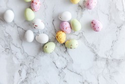 Happy Easter concept. Preparation for holiday. Easter pastel candy chocolate eggs sweets on trendy gray marble background. Simple minimalism flat lay top view copy space