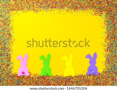 Happy Easter concept. Yellow paper background.Frame Color confectioners Sugar sprinkles.Traditional sweet decoration.Top View. Flat Lay