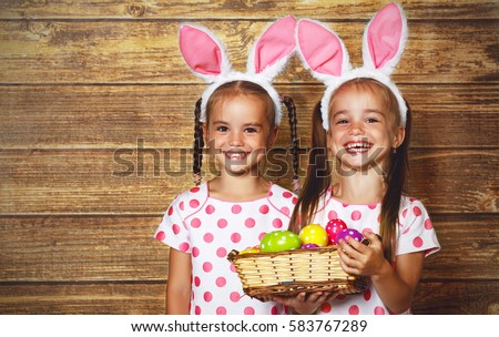 Happy easter! cute twins girls sisters dressed as rabbits with eggs on wooden background #583767289