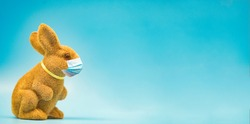 Happy Easter day.Rabbit in easter with mask medical during coronavirus covid19.Colorful eggs around rabbit.Healthcare, Holiday, Mask stay safe.Spring season.Happy easter banner blue background.