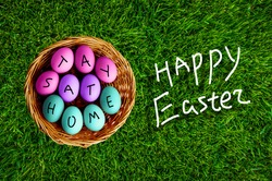 Happy Easter during Covid19, color eggs in the basket on the grass background, stay at home, title on the eggs