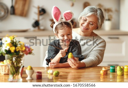 Happy easter! family grandmother and child granddaughter with ears hare getting ready for holiday