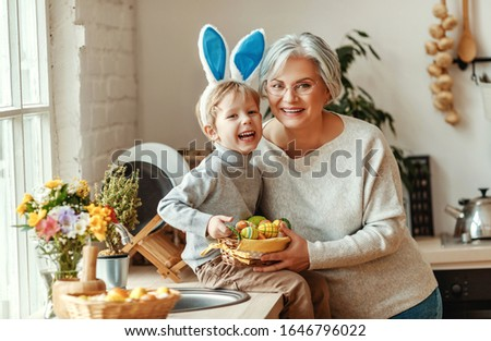 Happy easter! family grandmother and child grandson with ears hare getting ready for holiday