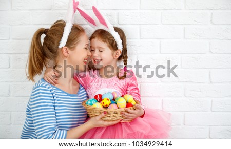 Happy easter! family mother and child daughter with ears hare getting ready for holiday #1034929414