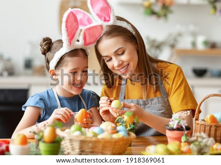 Happy easter! family: mother and child daughter with ears hare getting ready for holiday, paint eggs in the cozy kitchen at home