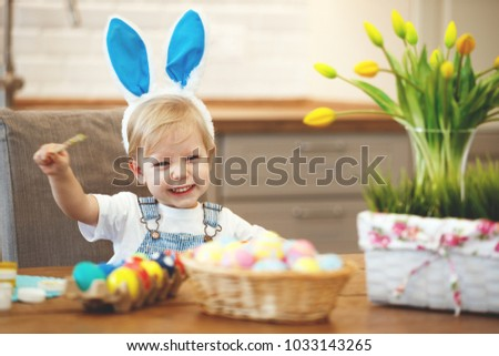 Happy easter! family mother and children paint eggs for the holiday