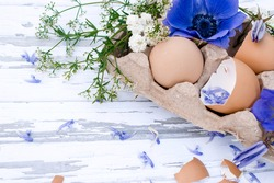 Happy Easter flat lay.Eggs with white and purple flowers on a white background.Copy space,top view, selective focus with shallow depth of field.