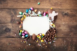 Happy Easter frame with greeting card with space for text,  chocolate eggs,  ribbon bows and candies on wooden background