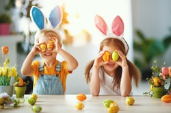 Happy easter! funny funny children boy and girl with ears hare getting ready for holiday