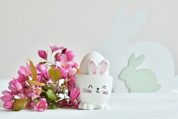Happy Easter holiday concept with cute bunny and fresh pinkflowers on white table background. Greeting card. Easter background. Copy spase. Selective focus