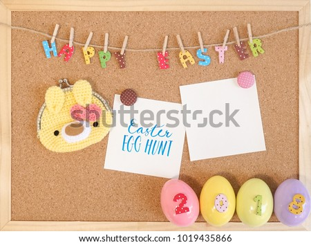 Happy Easter message 2018, colorful letters on cork board or notice board with a blank card and handmade crochet of Easter bunny coin purse.