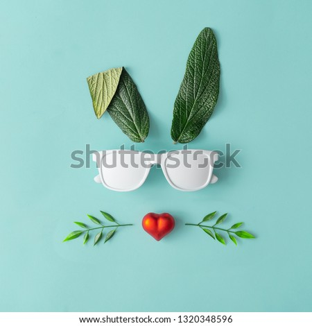 Happy Easter minimal concept. Bunny rabbit face made of natural green leaves with sunglasses and red heart on pastel blue background. Flat lay. #1320348596